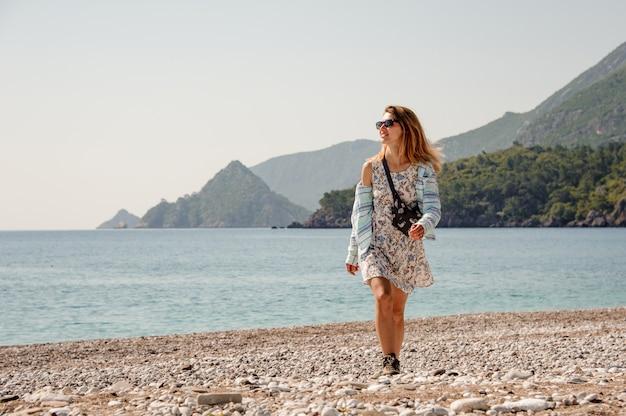 Moça no vestido claro na praia