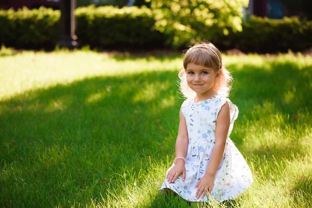 Moça pequena bonita outdoorin um parque.