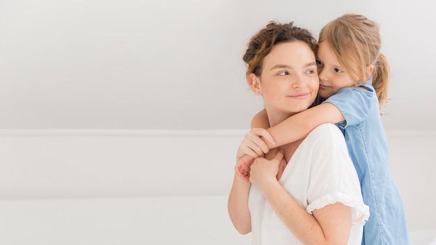 Moça que abraça sua mãe em casa