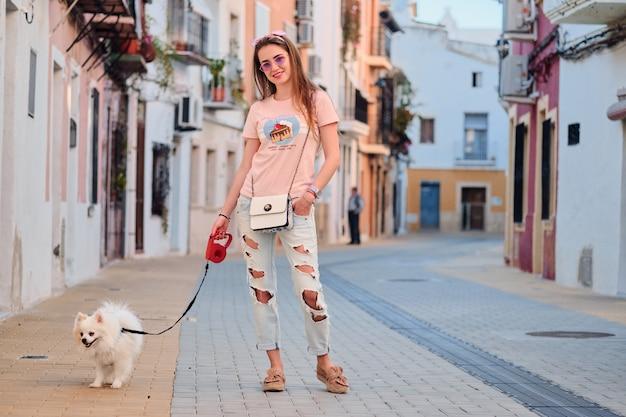Moça que anda com um pomeranian macio branco.
