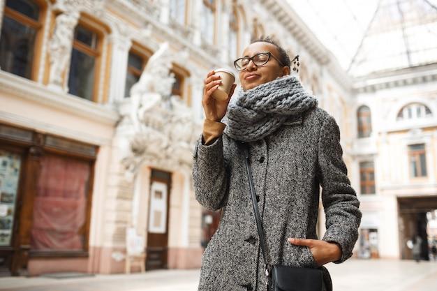 Moça que aprecia a bebida quente ao andar no dia frio.