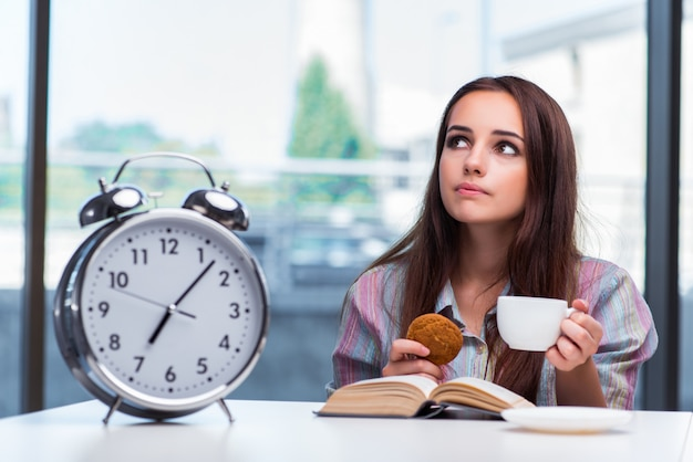 Moça que come o café da manhã na manhã