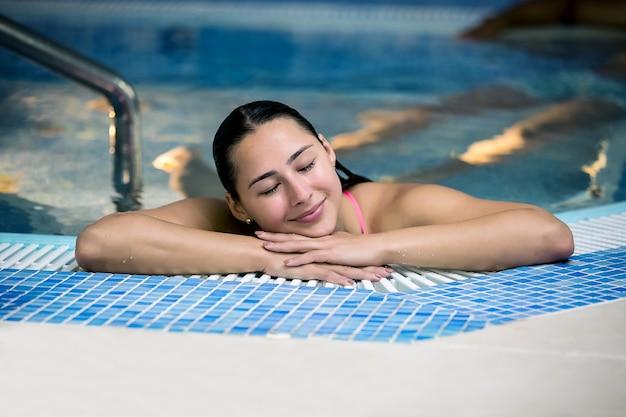 Moça que descansa na piscina