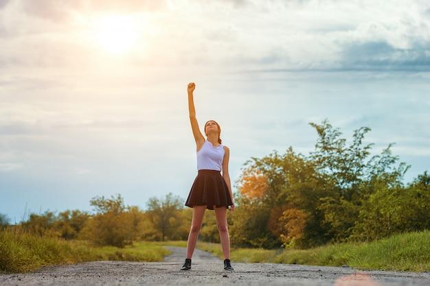 Moça que está na estrada com sua mão acima, o conceito do sucesso.