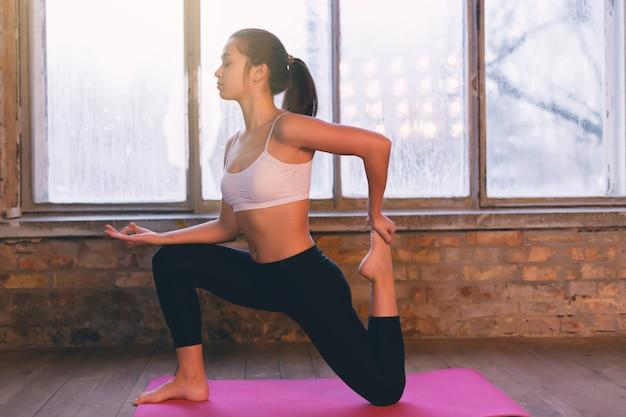 Moça que faz a ioga no assoalho em casa oposto à janela na manhã