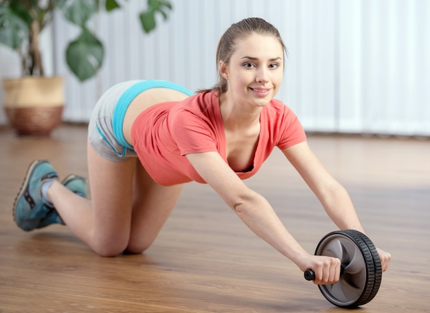 Moça que faz exercícios da aptidão no assoalho.