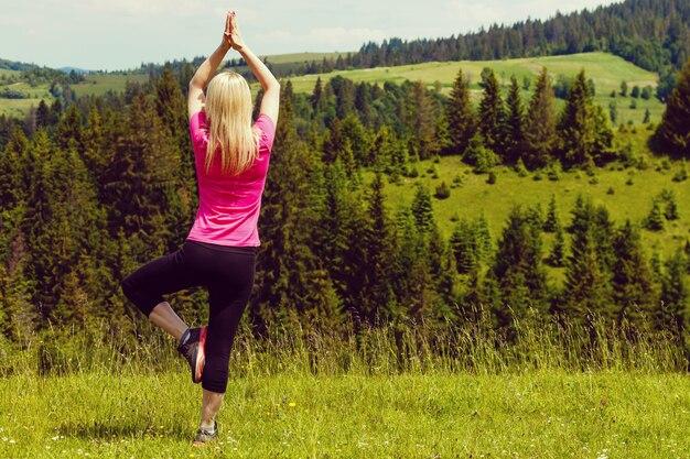 Moça que faz o exercício da aptidão da ioga exterior na paisagem bonita das montanhas.