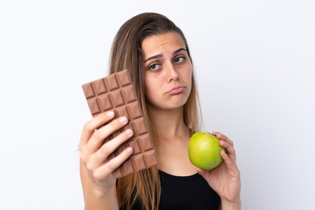Moça que guarda chocolate e uma maçã