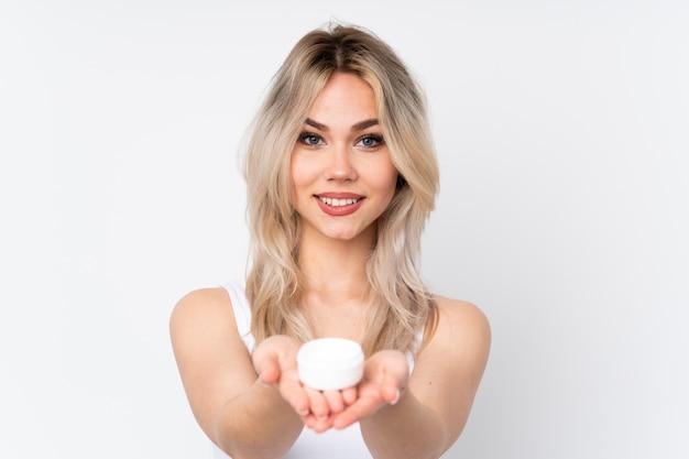 Moça que guarda cosmético sobre a parede isolada