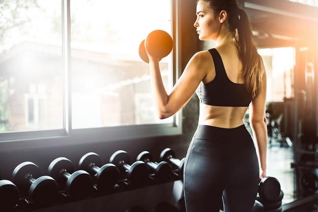 Moça que joga o dumbbell para exercitar na aptidão