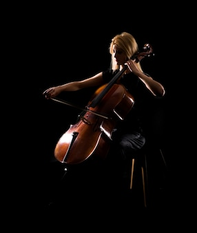 Moça que joga o violoncelo no fundo preto isolado