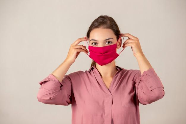 Moça que põe sobre uma máscara protetora durante uma pandemia de covid-19.