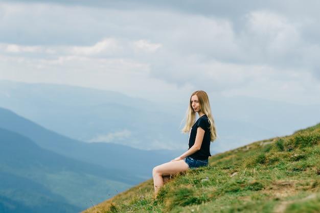Moça que relaxa e que aprecia a vista cênico no topo da montanha no verão.