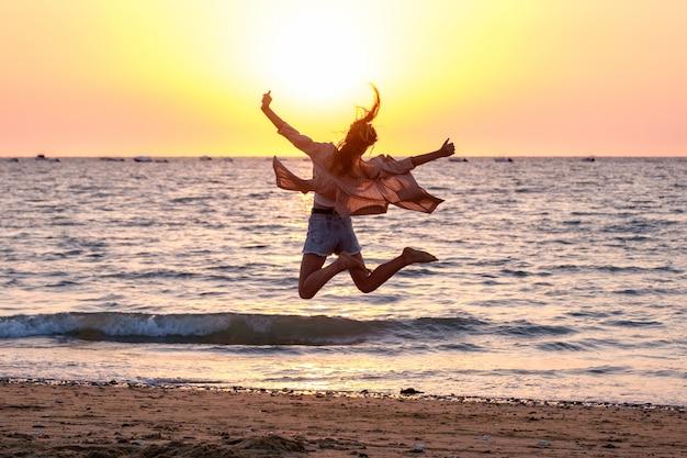 Moça que salta na praia no por do sol do verão.