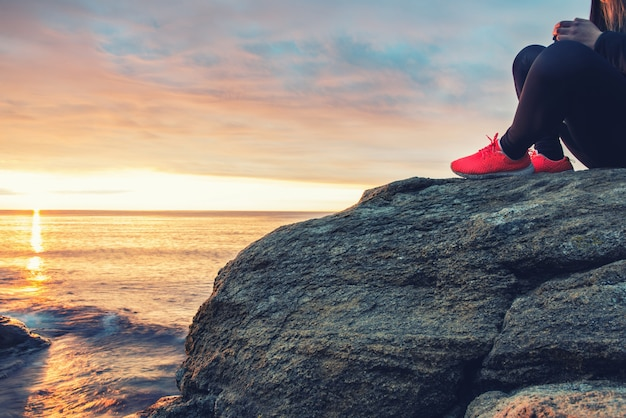 Moça que senta-se em uma rocha do mar que encontra o sol da manhã.