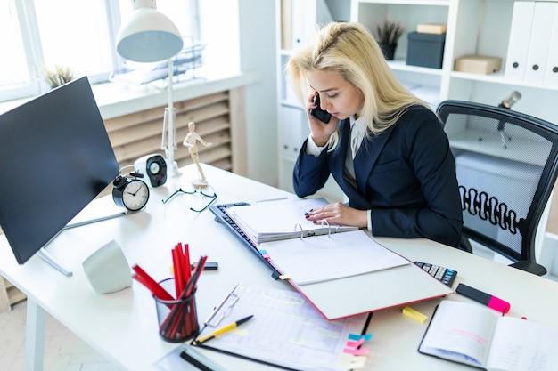 Moça que senta-se na mesa no escritório, falando no telefone e olhando originais.