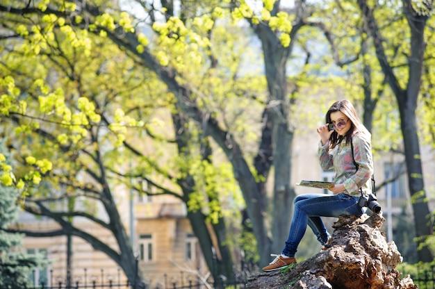 Moça que senta-se no parque e que lê um mapa