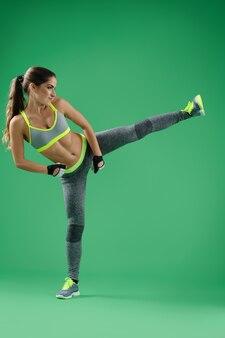 Moça que treina o pontapé lateral no estúdio no fundo verde