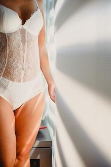 Moça que veste a roupa interior branca que levanta com luz natural, noface.