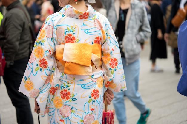 Moça que veste o quimono japonês que está na frente do templo de sensoji no tóquio, japão.