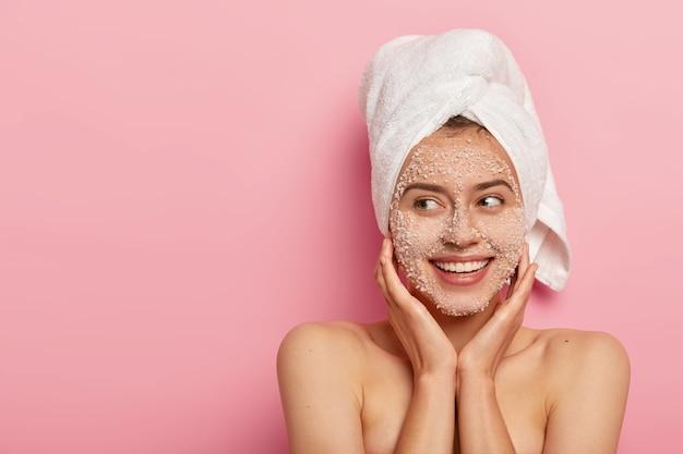 Moça satisfeita com expressão encantada, aplica produto de beleza natural no rosto, desobstrui os poros, tem sorriso charmoso, olha de lado, tem toalha enrolada na cabeça, tem corpo nu, pele sã
