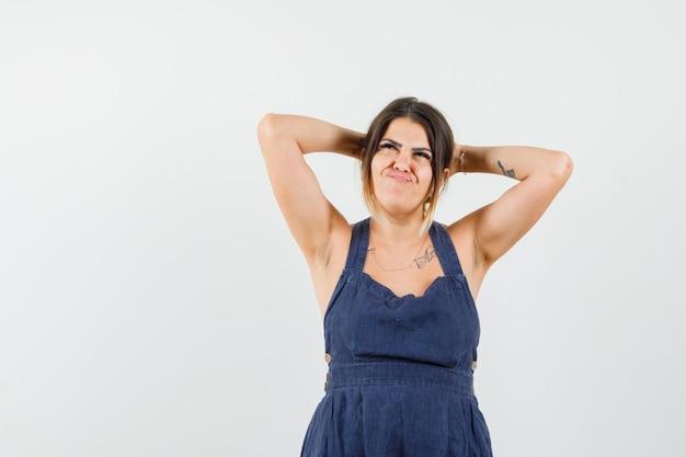 Moça segurando as mãos na cabeça em um vestido e parecendo pensativa