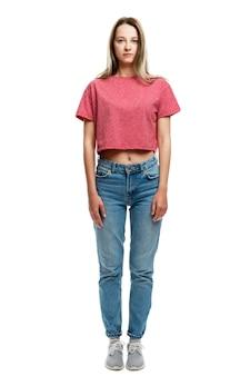 Moça séria em uma camiseta de alças vermelha e em calças de brim. altura toda. . vertical.