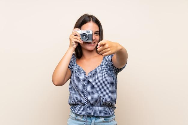 Moça sobre a parede isolada que prende uma câmera