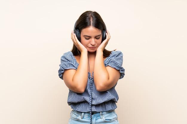 Moça sobre parede isolada, ouvindo música com fones de ouvido