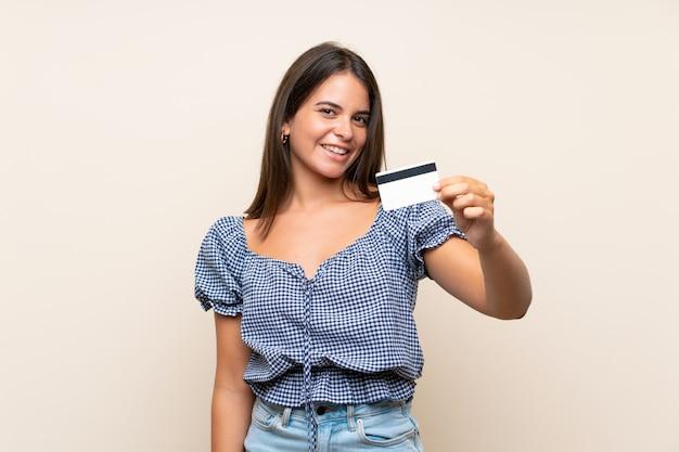 Moça sobre parede isolada, segurando um cartão de crédito