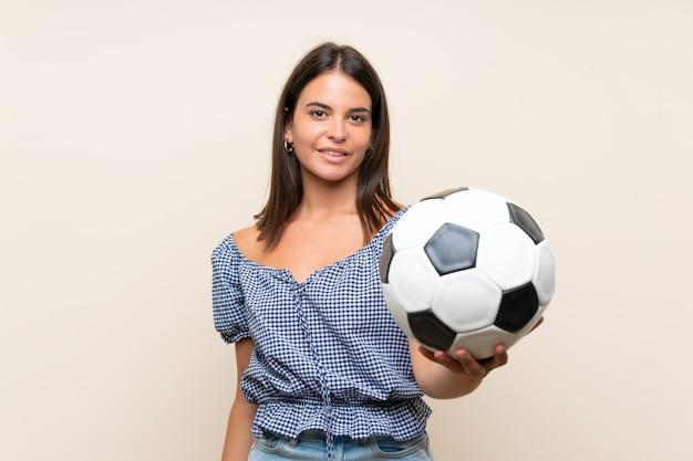 Moça sobre parede isolada, segurando uma bola de futebol