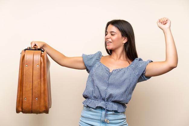 Moça sobre parede isolada, segurando uma maleta vintage