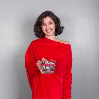 Moça sorridente com carrinho de compras e presentes