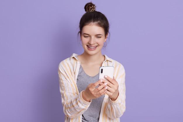 Moça sorridente com coque de cabelo, segurando o telefone inteligente moderno nas mãos e fazendo selfie