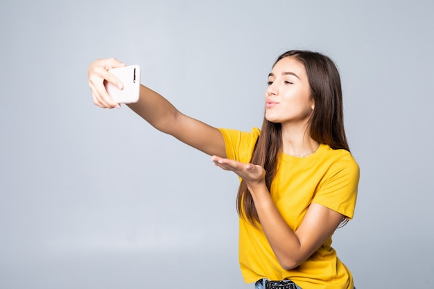 Moça sorridente fazendo foto de selfie em smartphone sobre parede cinza