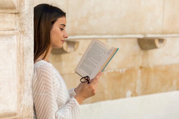 Moça sorridente, lendo o livro e segurando óculos