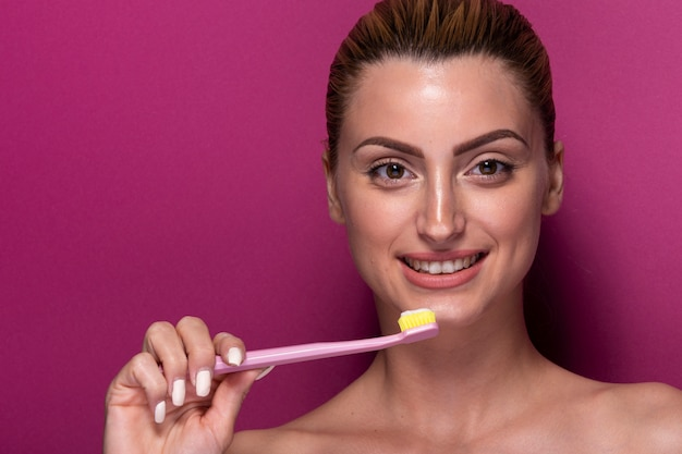 Moça sorridente segurando a escova de dentes