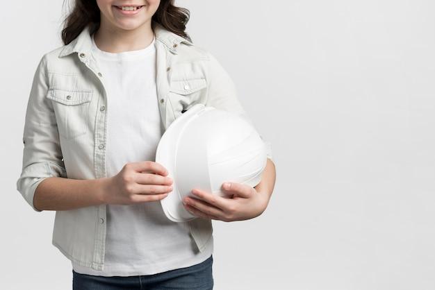Moça sorridente segurando capacete com espaço de cópia