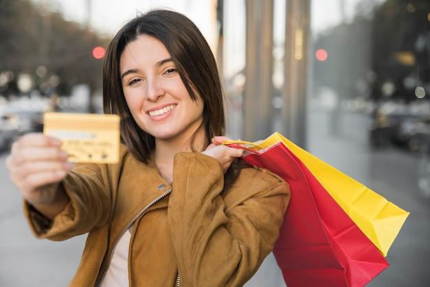 Moça sorridente segurando o cartão de plástico