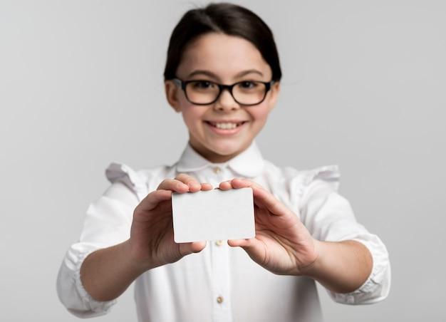 Moça sorridente segurando o cartão de visita