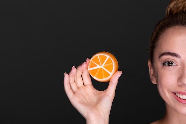 Moça sorridente segurando o produto de cuidados da pele