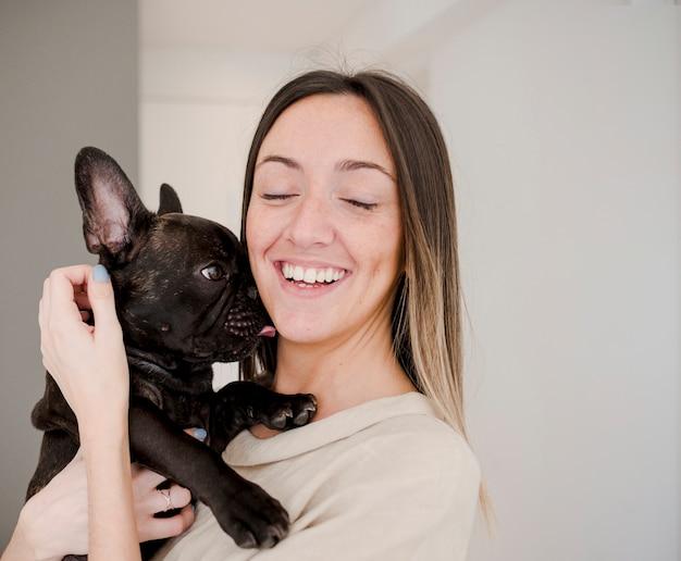 Moça sorridente segurando seu cachorro