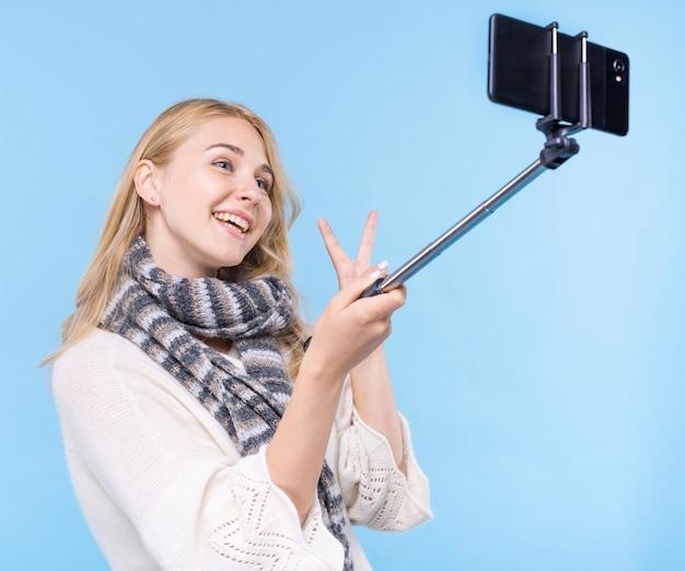 Moça sorridente tomando uma selfie