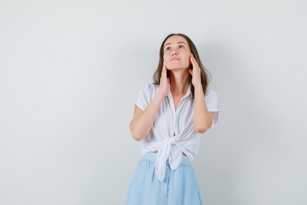 Moça tocando seu rosto com as mãos na blusa branca, saia azul e parecendo sensata