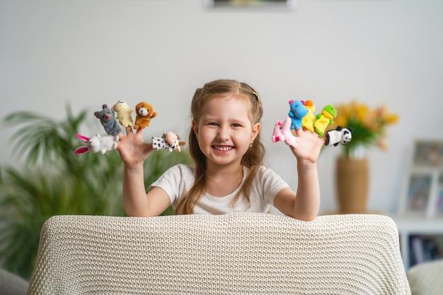 Moça tocando teatro. bonecos de dedo estão vestidos nas mãos da criança.