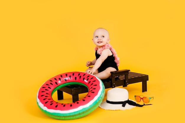 Moça vestida com um maiô preto e rosa, chapéu grande sentado na espreguiçadeira de madeira, isolado no fundo amarelo. conceito de férias de verão
