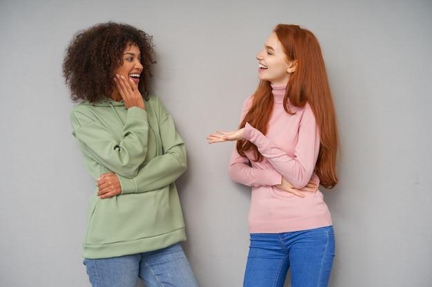 Moças alegres e adoráveis sorrindo positivamente enquanto se encontram e têm uma conversa agradável, usando roupas casuais confortáveis enquanto posam sobre uma parede cinza