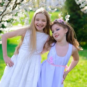Moças bonitas com olhos azuis em um vestido branco no jardim com macieiras florescendo se divertindo e apreciando o cheiro do jardim primavera