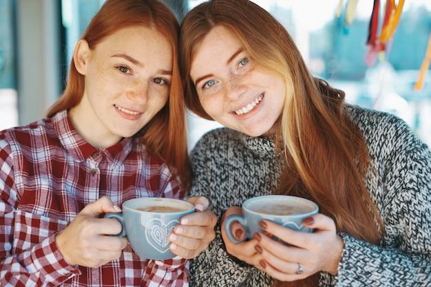 Moças bonitas de sorriso que levantam com café
