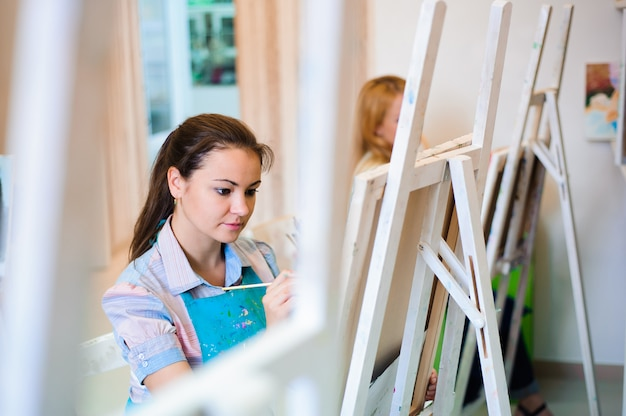 Moças bonitas desenham pinturas de uma lição de arte
